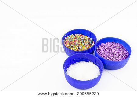 Three tapers with grated coconut and colorful dragees. White background.
