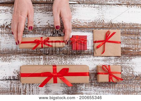 Present. Gift box closeup. Woman holding small gift box with ribbon.