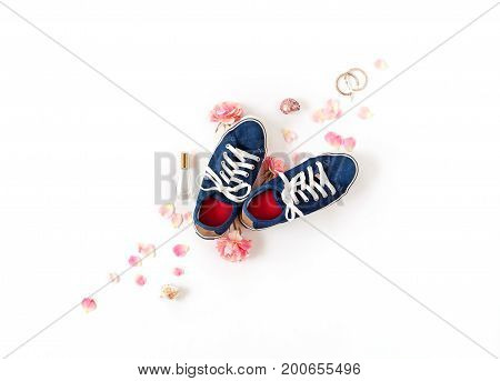 Denim Gumshoes With White Laces Isolated. Pink Petals And Feminine Accessories Flat Lay.