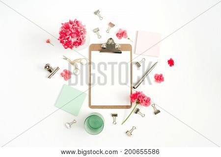 Flat lay home office desk. Clipboard with copy space for text red flowers accessories mint diary on white background. Top view mock up women background.