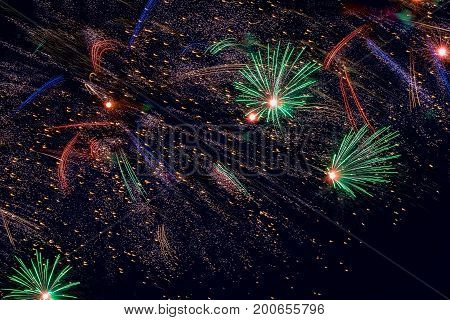 Holiday Fireworks with sparks on black sky as stars, universe, comets. New Year holidays salute.