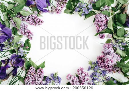 Frame of lilac flowers branches leaves and petals with space for text on white background. Flat lay top view