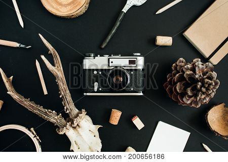 Top view flat lay hipster photographer concept. Retro camera goat horns handmade spoon craft diary cone on black chalk board background.