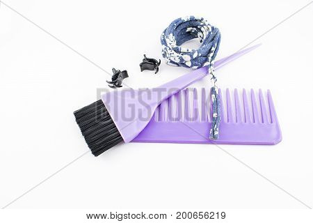 Brush for hair dye and comb for combing. Clips and ribbons to collect hair. On white background.