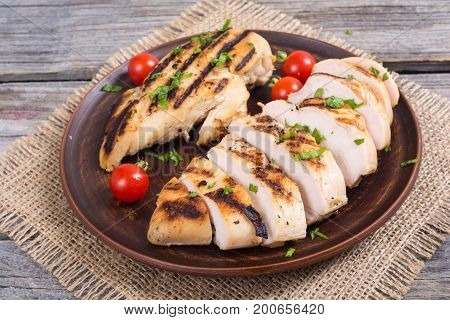 Grilled chicken breast with tomato and parsley . On wooden background .
