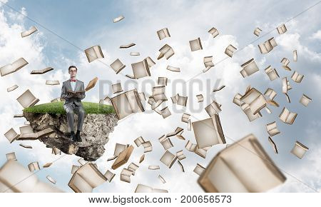Funny man in red glasses and suit sitting on floating island and reading book
