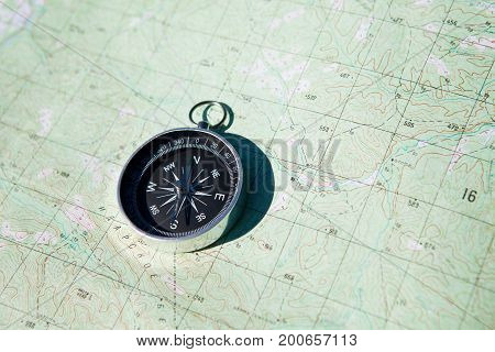 Compass over map background. Top view. Travel concept.