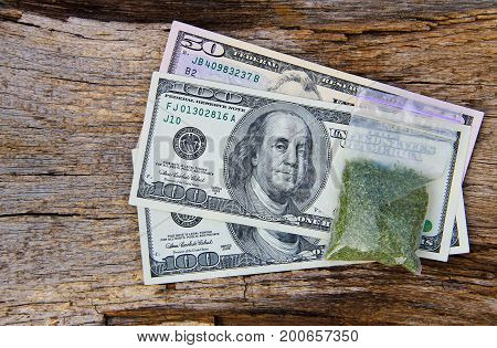 Dollars And Marijuana In Packet On Wooden Background