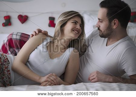 Beautiful woman and attractive man lying on bed together