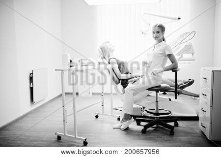 Beuatiful Female Dentist Posing And Smiling With Her Lovely Patient Laying On A Dental Chair In Red-