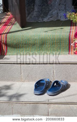 Blue sliders on steps of a house with open door, curtain lace and green-red footcloth