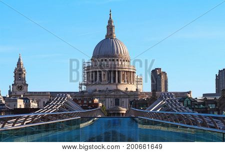St Paul's cathedral seen from a narrow alley enclosed by glass and brick buildings in the morning dawn.London, United Kingdom.
