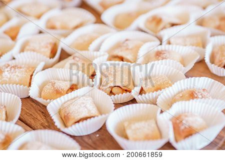 Set of  homemade fresh cookies dusted powdered sugar in white paper wrapper on wooden background.Sweet cookies with jam