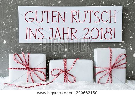 Label With German Text Guten Rutsch Ins Jahr 2018 Means Happy New Year 2018. Three Christmas Gifts Or Presents On Snow. Cement Wall As Background With Snowflakes. Modern And Urban Style.