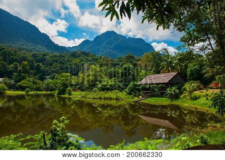 Traditional Wooden House Near The Lake And Mountain In The Background. Kuching To Sarawak Culture Vi