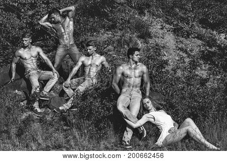 people of men with muscular sexy body and six packs on torso in jeans and pretty woman in dress sunny outdoor on natural background black and white