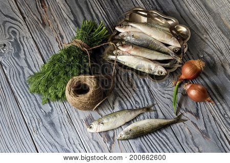 Fresh fish boops and vegetables on wooden table close-up.
