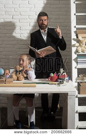 Family by desk with school supplies. Girl and father on white brick background. Schoolgirl and dad with distracted and serious faces play with globe and hold book. Home education and school concept
