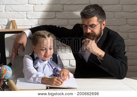 Family Works At Desk With School Supplies. Girl And Father