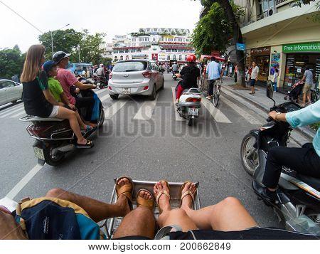 HANOI, VIETNAM - AUGUST 16, 2017: Tourists taking a cyclo ride through the streets in Hanoi, Vietnam.