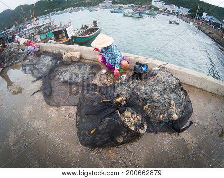 NAM DU Island, VIETNAM - JULY 25, 2017:  Woman repairing a fishing net in Hon Tre pier in Nam Duisland, Kien Giang, Vietnam