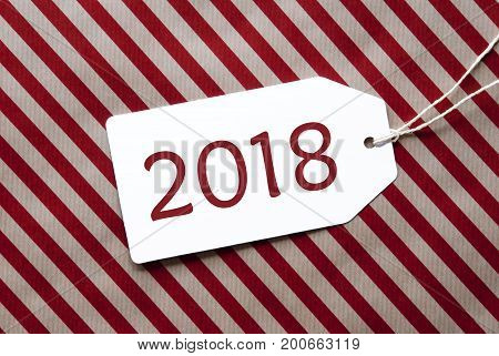One Label On A Red And Brown Striped Wrapping Paper. Textured Background. Tag With Ribbon. English Text 2018 For Happy New Year Greetings