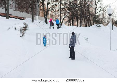 Caring dad walks with his son at weekends in the winter frosty day.