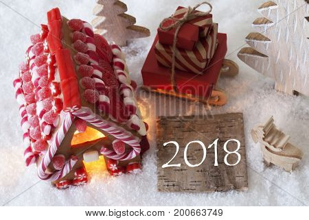 Label With Text 2018 For Happy New Year. Gingerbread House On Snow With Christmas Decoration Like Trees And Moose. Sleigh With Christmas Gifts Or Presents.