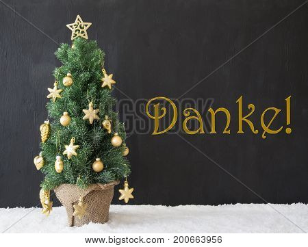 German Text Danke Means Thank You. Golden Decorated Christmas Tree With Black Concrete Or Cement Background. Modern Urban Style With Snow