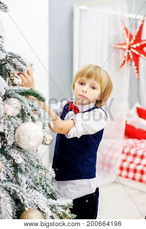 Little boy decorates a Christmas tree in the room. Concept winter lifestyle Merry Christmas.