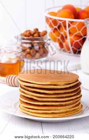 Stack of homemade american pancakes served with honey, hazelnuts and apricots on white plate