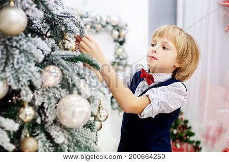 The child decorates a Christmas tree in the room. Concept winter lifestyle Merry Christmas.