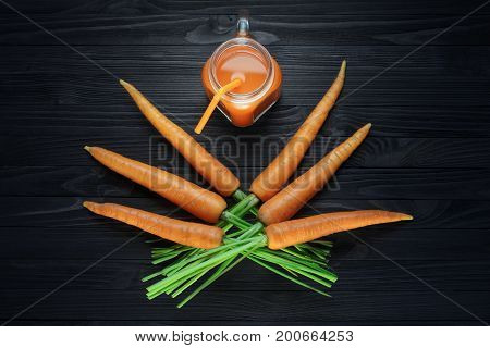 Fresh carrot juice in a glass jar with handle on a black wooden table. Carrot smoothie in a glass mug with orange straw and a bunch of fresh carrots top view