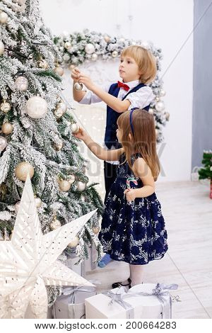 Little brother and sister adorns the Christmas tree in the room. Concept winter lifestyle Merry Christmas.