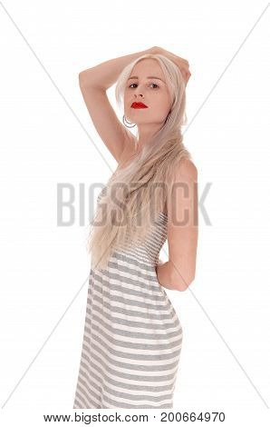 A beautiful serious looking woman with red lips standing in a light gray dress with one hand on her head isolated for white background