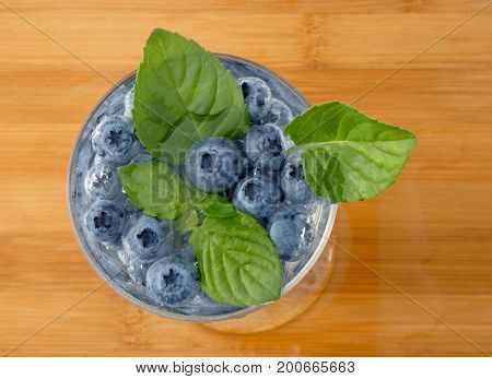 Blueberries in glass of water on a wooden board