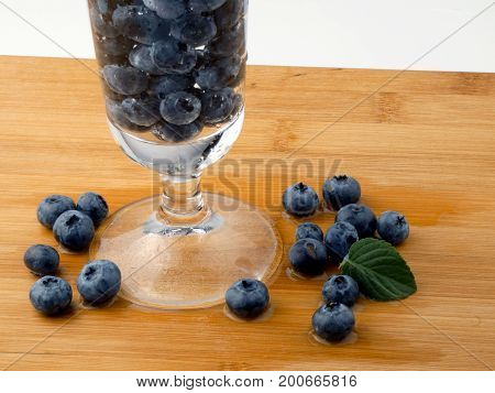 Blueberries in glass of water isolated on white background