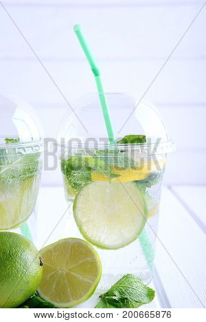 Refreshing summer drink. Lime and mint mohito in plastic cocktail glasses with green straws.