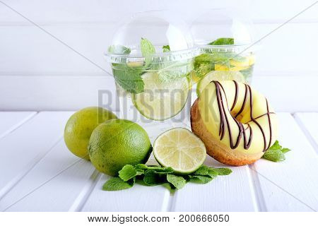 Refreshing summer drink. Lime and mint mohito in plastic cocktail glasses with green straws and sweet doughnut with green icing.