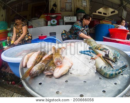 HO CHI MINH CITY, VIETNAM - JULY 25, 2017:  Women selling fish at the Ben Thanh market in Saigon (Ho Chi Minh City), Vietnam