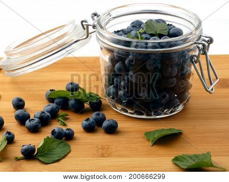 Blueberries in a glass jar on a wooden board isolated on white background