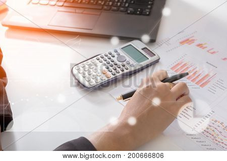 Young finance market analyst working at sunny office on laptop while sitting at white table.Businessman analyze document and the calculator in hands.Graphs and diagram on notebook screen