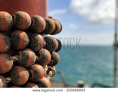 Wooden Parrel Beads on a red mast of a yacht with a blurred background of the sea sky and horizon with space for text. Parrel beads are used to attach sail to mast to allow sail to slide up and down.