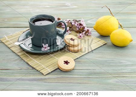 A cup of fragrant tea with lemons and cookies on the wooden table closeup