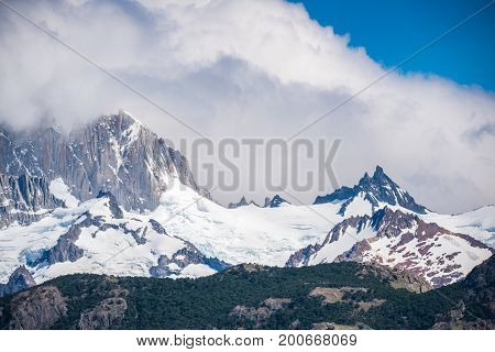 Snow-capped mountain top and fluffy cloud. Landscape of mountains with clouds in the afternoon. Snow-capped mountain tops are shrouded in clouds. Fluffy clouds cover parts of the rocky mountains. Sunlight highlights the snowy peaks of the mountains.