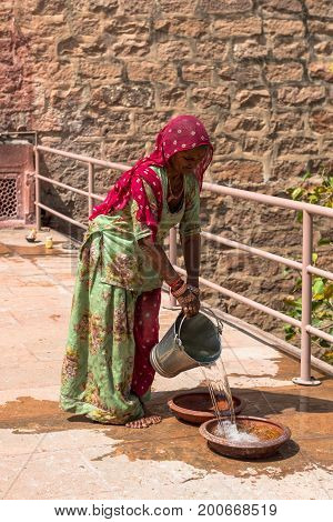 JODHPUR RAJASTHAN INDIA -MARCH 05 2016: Vertical picture of Indian woman spilling water at Mehrangarh Fort in Jodhpur the blue city of Rajasthan in India.