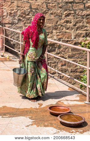 JODHPUR RAJASTHAN INDIA -MARCH 05 2016: Vertical picture of Indian woman carrying a bucket at Mehrangarh Fort in Jodhpur the blue city of Rajasthan in India.