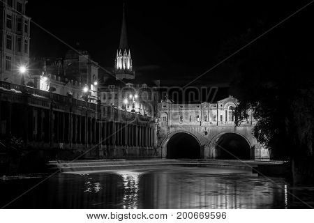 Pulteney Bridge and weir at night black and white. Palladian bridge in Bath Somerset UK with River Avon flowing underneath at night