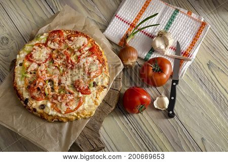 Pizza and vegetables on a wooden table close-up in a rustic style