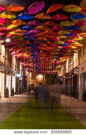 BATH UK - 19 AUG 2017 Shoppers and umbrellas on St. Lawrence Steet. Public art installation on shopping street with many people walking at night